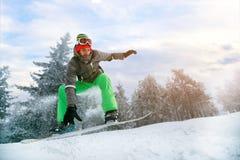 Surfeur dans le saut à la station de sports d'hiver dans la montagne Images libres de droits