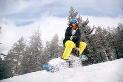 Surfeur de fille dans le saut à la station de sports d'hiver dans la montagne Photo libre de droits