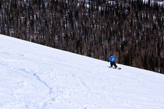 Surfeur de jeune fille dans le mouvement sur le surf des neiges en montagnes Photographie stock libre de droits