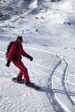 Surfeur en descendant sur la neige outre de la pente de piste dans le morni d'hiver du soleil Images libres de droits