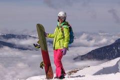 Surfeur heureusement de sourire de fille en montagnes d'hiver Photographie stock