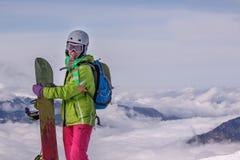 Surfeur heureusement de sourire de fille en montagnes d'hiver au-dessus des nuages Image stock