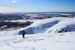 Surfeur montant la montagne de neige et le paysage arctique derrière lui Photo stock