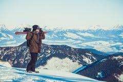 Surfeur se tenant au dessus même d'une montagne et tenant le surf des neiges sur son épaule avec le beau paysage avant lui Photo stock