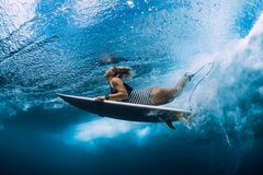 Surfgirl with surfboard dive underwater with under ocean wave. Surfgirl with surfboard dive underwater with under sea wave royalty free stock photo