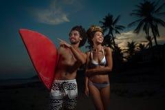Surfig-Paare, die auf dem Strand aufwerfen Stockfoto