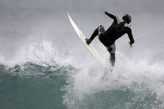 Surfing 001. A surfer rides the lip of a wave Stock Images
