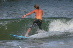 Surfing. Young man surfing on a windy day at the beach Royalty Free Stock Photo