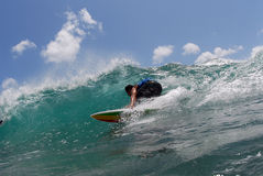 Surfing. A shortboard surfer surfing a beautiful wave in hawaii about to get a tube ride royalty free stock images