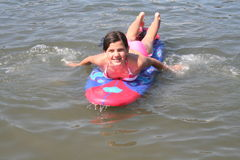 Surfing. Girl swimming towards shore on a surf board Stock Photography