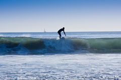 Surfing. Silhouette of a man surfing a wave with blue sky in the background Royalty Free Stock Image