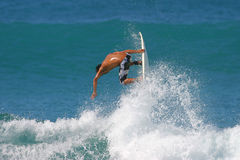 Surfing Air. A surfer catches air while surfing in Honolulu, Hawaii Stock Image