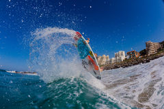 Surfing Air Water Action. Flying surfboard and pro surfer Josh Redman punts are air turn maneuvers off the wave lip with fins and board colors and sea spray Stock Photo