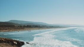 Surfing in Atlantic Ocean, Morocco, many people on the beach, big waves and clear sky and mountains on horizon