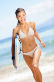 Surfing beach woman - happy surfer girl running royalty free stock photos