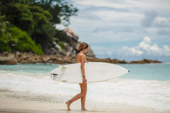 Surfing beautiful woman on the beach Royalty Free Stock Photos