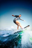 Surfing at blue ocean. Young man balanced on kiteboard, wakeboard. Surfing at blue sea. Young man balanced on wave on surfboard.  Wake surf outdoor lifestyle Royalty Free Stock Images