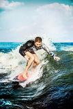 Surfing at blue sea. Young man touched wave on surfboard. Stock Image