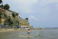 Surfing boy at Nettuno sea.Italian coast and beach.Tourist destination. Surfing boy.Nettuno,sea italian coast.Town and comune of the province of Rome in the royalty free stock photos