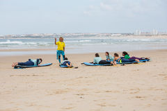 Surfing coach instructs novice surfers on the beach near the open water. Portugal, Peniche - October 10, 2016: Surfing coach instructs novice surfers on the Stock Photos