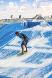 Surfing on Cruise Ship. Fort Lauderdale, Florida - Jan. 12, 2013:  Man surfing on the FlowRider aboard the Oasis of the Seas.  Royal Caribbean offers this Stock Photos