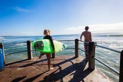 Surfing dziewczyny chłopiec fala mola skok fotografia stock