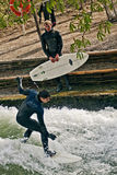 Surfing at Englischer Garden in Munich. Great attraction in Munich, surfer rides the artificial wave on the Eisbach, small river across the Englischer Garten Stock Images