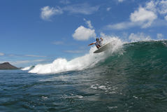Surfing fins out. A shortboard surfer doing a off the lip with all fins out on a beautiful wave in hawaii Stock Image