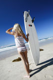 Surfing girl. Girl with surfboard checking surf Royalty Free Stock Images