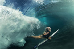 Surfing girl having fun under wave stock images
