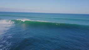 Surfing in huge white foamy waves in blue turquoise ocean water on sunny summer day in 4k aerial seascape drone view stock footage