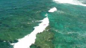 Surfing in huge white foamy waves crash in deep blue turquoise ocean water in stunning 4k aerial drone camera seascape. Surfing in huge white foamy waves crash stock video footage