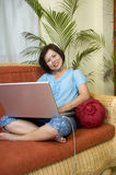 Surfing the internet. Woman sitting on her sofa and working with computer Royalty Free Stock Images