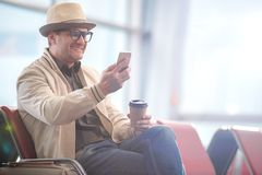 Delighted middle-aged tourist is holding smartphone. Surfing internet. Joyful adult man in hat and glasses is waiting for flight at airport lounge. He is using Royalty Free Stock Photo
