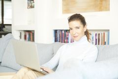 Surfing on the internet from my cosy sofa. An attractive smiling woman using her laptop while relaxing at home on the sofa Stock Photos