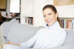 Surfing on the internet from my cosy sofa. An attractive smiling woman using her laptop while relaxing at home on the sofa Royalty Free Stock Image