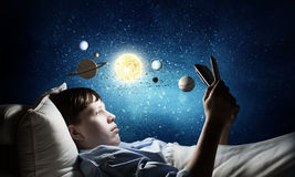 Surfing internet before sleep. Teenage boy in pajamas lying in bed using tablet pc royalty free stock images