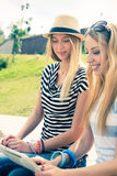 Surfing internet. Two young female friends sitting on steps and using tablet pc royalty free stock images