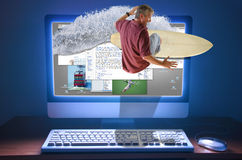 Surfing Internet Web Surfer Surfboard Wave. An internet web surfer is literally surfing a wave right through the computer screen with web pages and photos on the Royalty Free Stock Photography