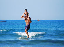 Surfing with kids - shoulder joyful ride Royalty Free Stock Photos