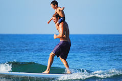 Surfing with kids - shoulder joyful ride Stock Images