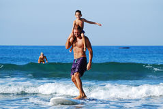 Man and boy on surf board. Man and boy riding wave on surf board on sunny day Royalty Free Stock Images