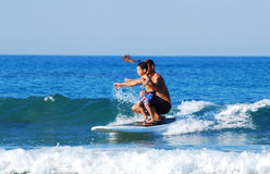 Father and son surfing the wave Stock Photos