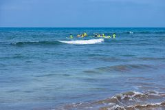 Surfing lesson in Maspalomas: group of surfboard learners with instructors in the sea. Maspalomas, Spain - July 18 2017. Surfing lesson in Maspalomas: group of Royalty Free Stock Photos