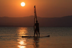 Surfing man silhouette again a beautiful sunset as background. Stock Photography