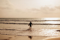 Surfing man silhouette in waves Royalty Free Stock Photo