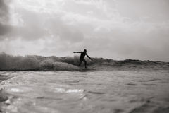 Surfing man in waves monochrome. Surfing man silhouette in waves monochrome Royalty Free Stock Photos