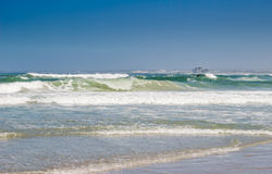 Surfing at Melkbosstrand beach with Koeberg Nuclear Power Statio. N in background - South Africa Stock Image