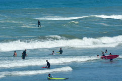 Surfing in Muriwai beach - New Zealand. MURIWAI, NZL - JAN 01 2015:Visitors surf in Muriwai beach.It's a very popular beach in New Zealand known for it beauty royalty free stock photos