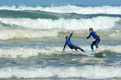 Surfing in Muriwai beach - New Zealand Stock Photo
